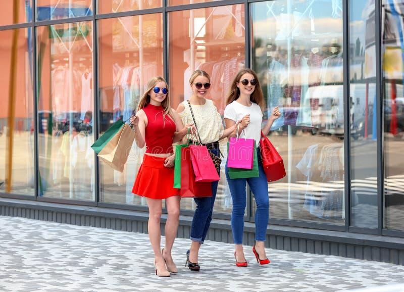 Mujeres jovenes con los bolsos de compras que caminan en la calle de la ciudad imagenes de archivo