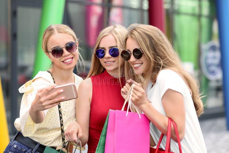 Mujeres jovenes con los bolsos de compras que toman el selfie en la calle de la ciudad fotos de archivo