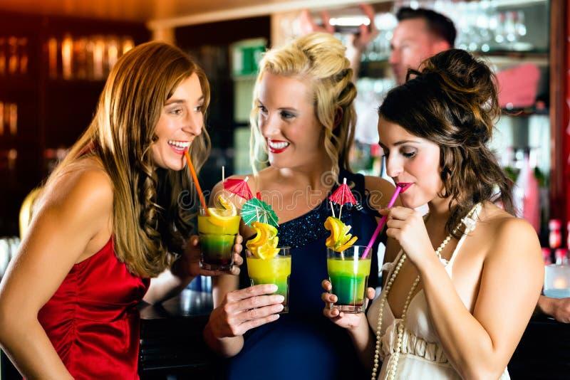 Mujeres jovenes con los cócteles en club o barra foto de archivo libre de regalías