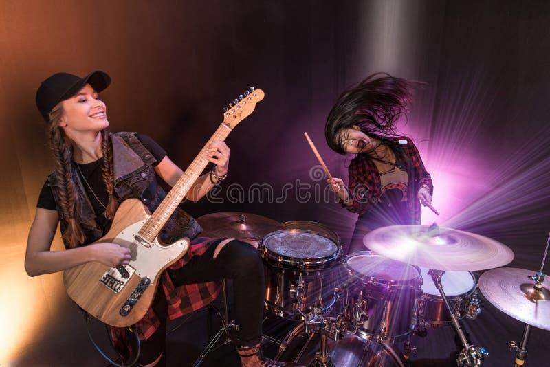Mujeres jovenes con los tambores fijados y la guitarra eléctrica que realiza concierto de rock en etapa fotos de archivo