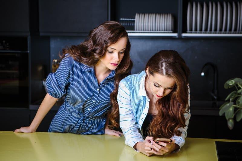 Mujeres jovenes de los gemelos bonitos junto en un cuarto de la cocina, estilo sport fotografía de archivo libre de regalías