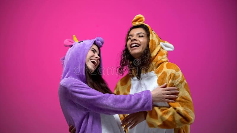 Mujeres jovenes divertidas que llevan el unicornio y los pijamas de la jirafa, riendo, entretenimiento fotos de archivo