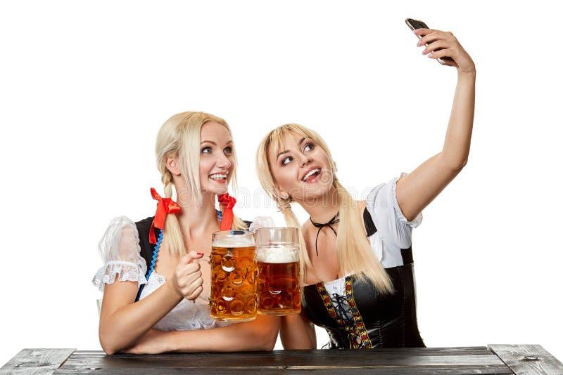 Mujeres jovenes en la ropa bávara tradicional, dirndl o tracht, en el fondo blanco fotografía de archivo libre de regalías