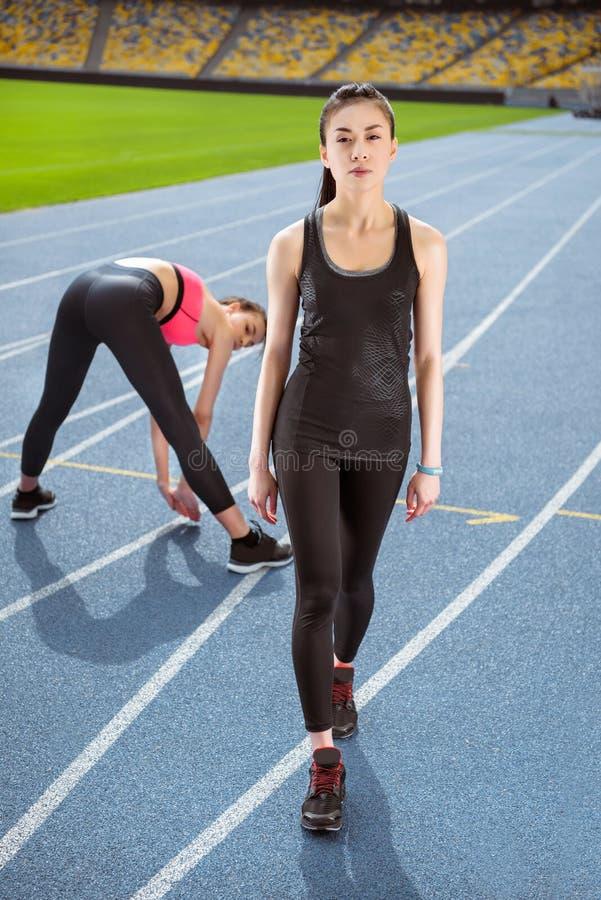 Mujeres jovenes en ropa de deportes que ejercitan en estadio corriente de la pista fotografía de archivo
