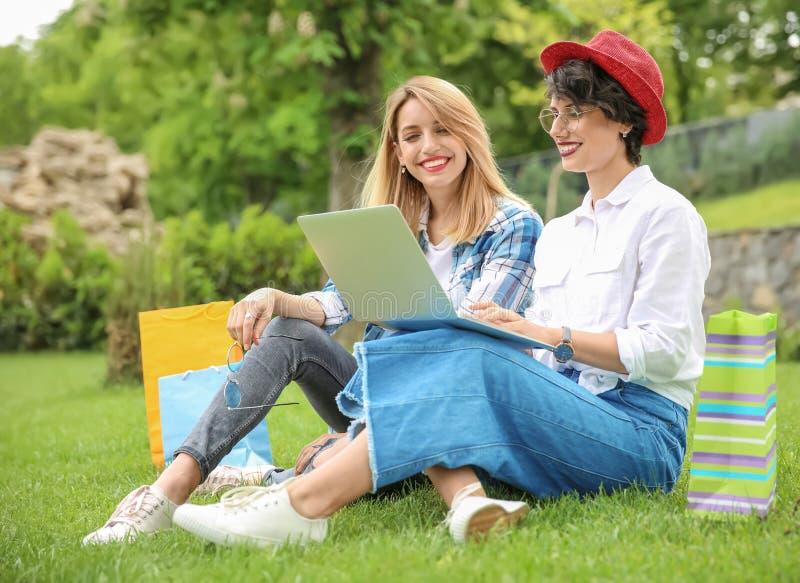 Mujeres jovenes en ropa elegante con el ordenador portátil al aire libre fotografía de archivo