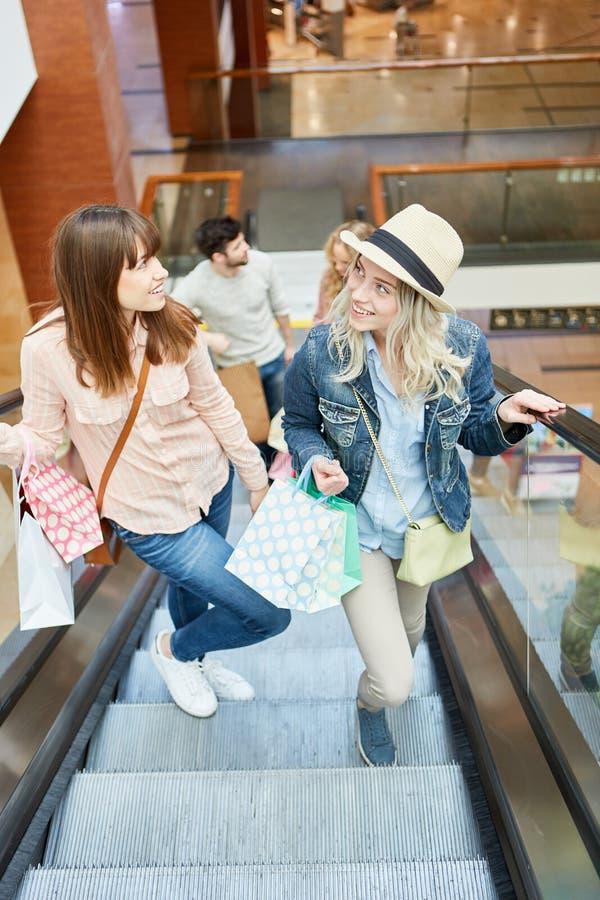 Mujeres jovenes en una escalera móvil imagen de archivo
