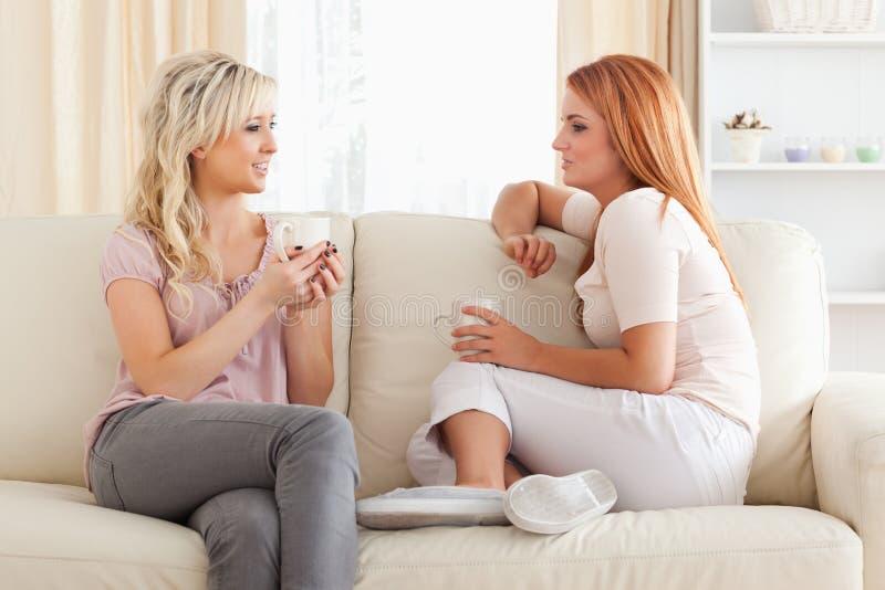 Mujeres jovenes encantadoras que se sientan en un sofá con las tazas imagen de archivo