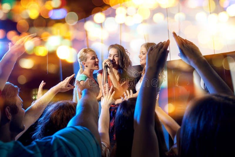 Mujeres jovenes felices que cantan Karaoke en club de noche imagenes de archivo