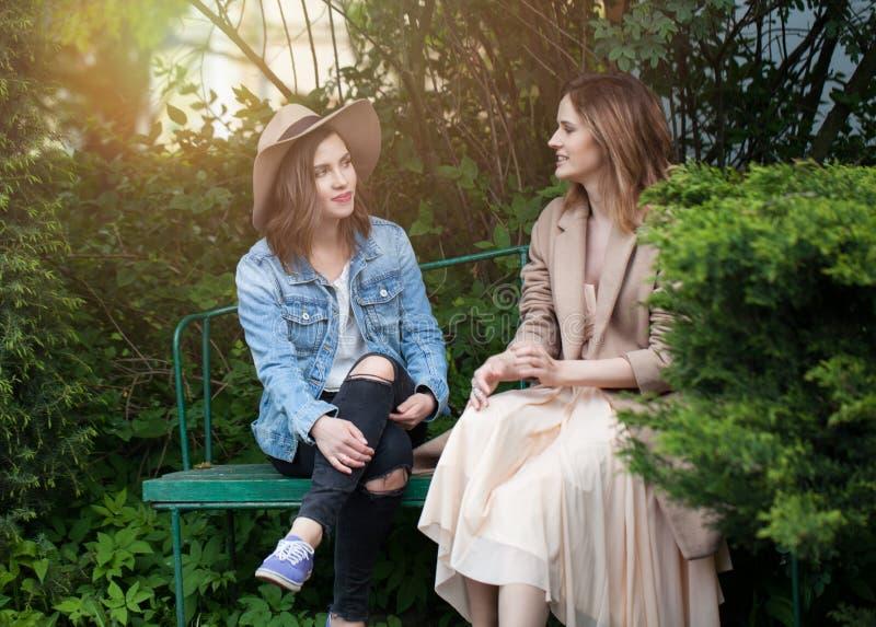 Mujeres jovenes felices que charlan en parque en el fondo del follaje del verdor, retrato de la forma de vida imagen de archivo