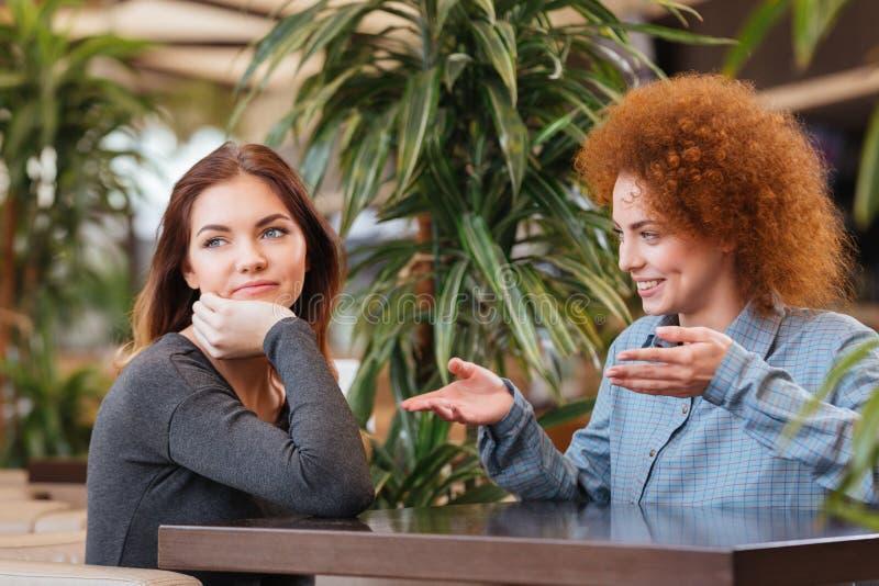 Mujeres jovenes felices y tristes que hablan en café imagen de archivo
