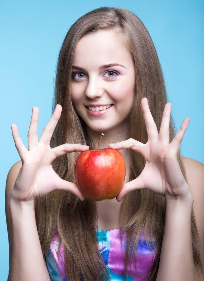 Mujeres jovenes hermosas con la manzana roja en el fondo azul imagenes de archivo
