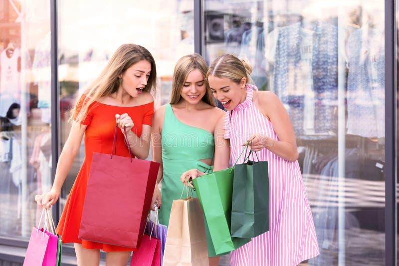 Mujeres jovenes hermosas con los bolsos de compras cerca de la tienda en la calle de la ciudad imágenes de archivo libres de regalías
