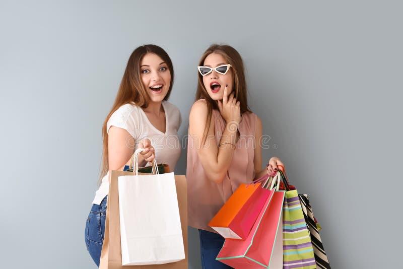 Mujeres jovenes hermosas con los bolsos de compras en fondo ligero imágenes de archivo libres de regalías
