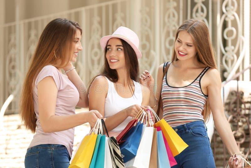 Mujeres jovenes hermosas con los bolsos de compras en la calle de la ciudad foto de archivo