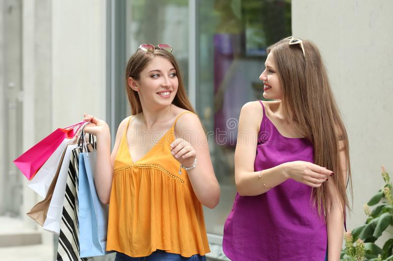 Mujeres jovenes hermosas con los bolsos de compras en la calle de la ciudad fotos de archivo libres de regalías
