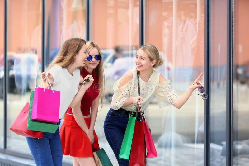Mujeres jovenes hermosas con los bolsos de compras que miran el escaparate de la tienda imágenes de archivo libres de regalías