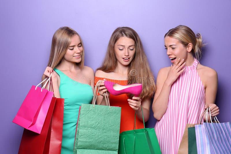 Mujeres jovenes hermosas con los nuevos zapatos y bolsos de compras en fondo del color foto de archivo libre de regalías