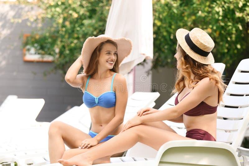 Mujeres jovenes hermosas en el bikini que descansa sobre sunbeds al aire libre imágenes de archivo libres de regalías
