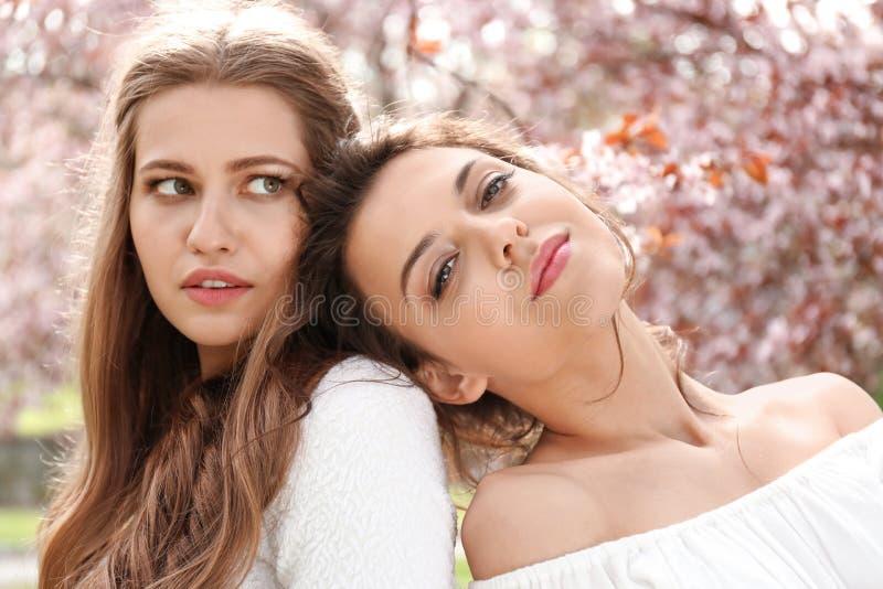 Mujeres jovenes hermosas en parque con los árboles florecientes el día de primavera imagenes de archivo