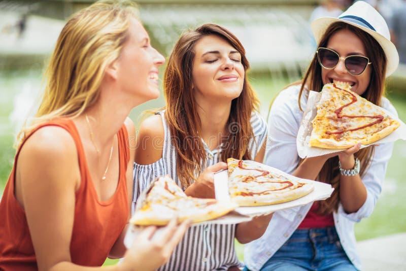 Mujeres jovenes hermosas que comen la pizza despu?s de hacer compras, divirti?ndose junto imágenes de archivo libres de regalías