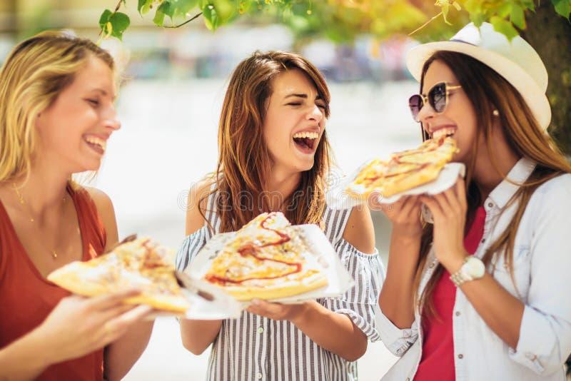 Mujeres jovenes hermosas que comen la pizza despu?s de hacer compras, divirti?ndose junto imagen de archivo