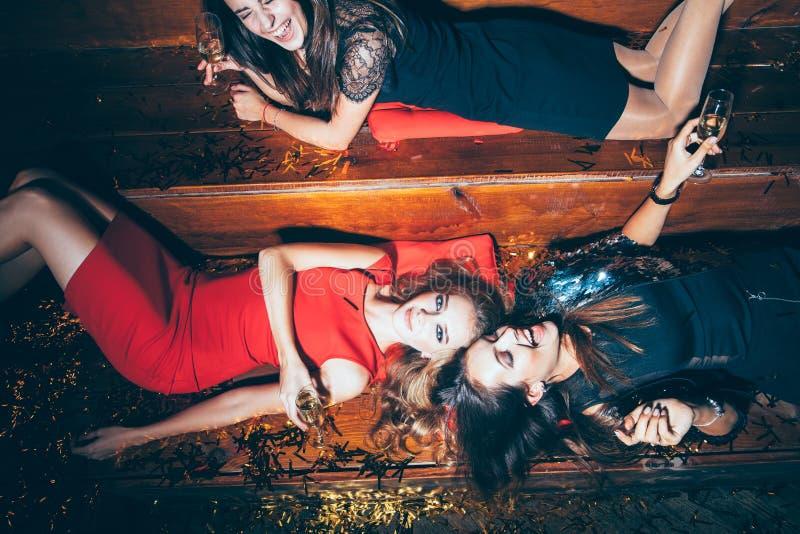 Mujeres jovenes hermosas que se divierten en el partido loco que miente en el flo foto de archivo
