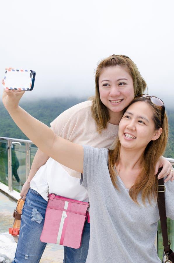 Mujeres jovenes hermosas que usan un teléfono móvil imagen de archivo