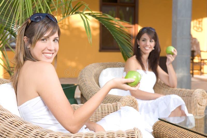 Mujeres jovenes hermosas relajadas comiendo una manzana imagen de archivo libre de regalías