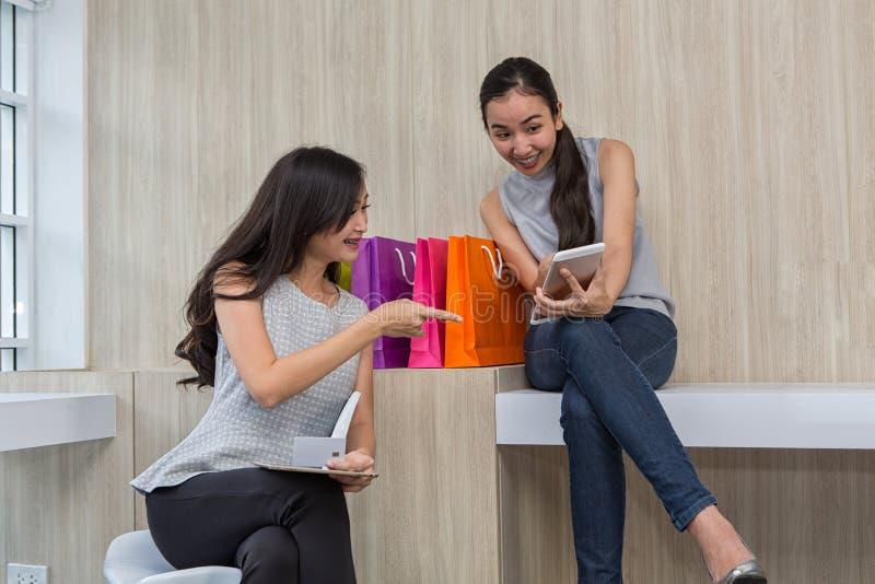 Mujeres jovenes hermosas usando el teléfono móvil y la tableta digitales en cafetería Las mujeres son felices con la historia en  imagenes de archivo