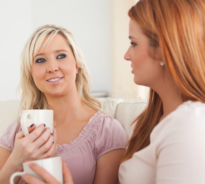 Mujeres jovenes lindas que se sientan en un sofá con las tazas imagenes de archivo