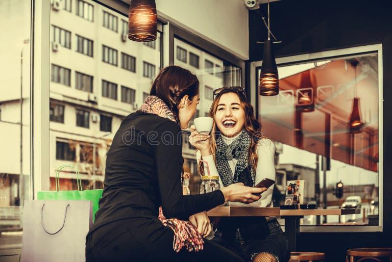 Mujeres jovenes que beben el café en tienda del cofe fotografía de archivo