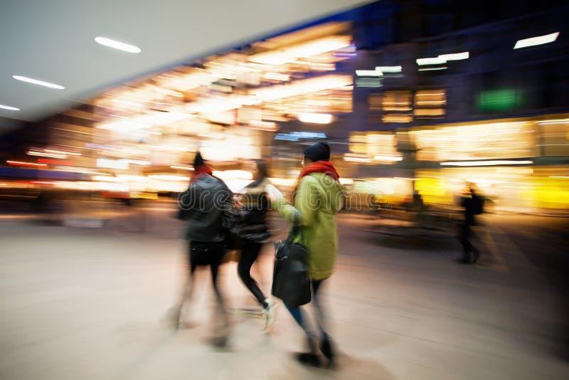 Mujeres jovenes que caminan abajo de la calle de las compras en la oscuridad imagen de archivo