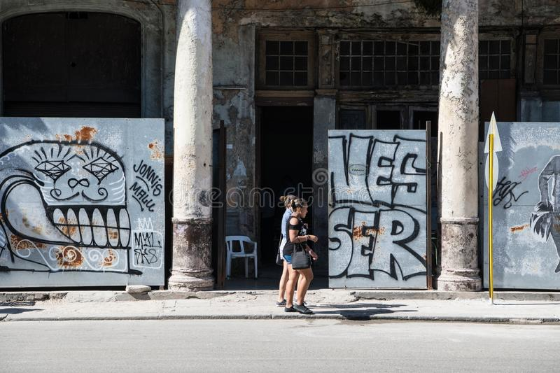 Mujeres jovenes que caminan delante de la pintada y del architectur colonial mórbido, La Habana, Cuba imagenes de archivo