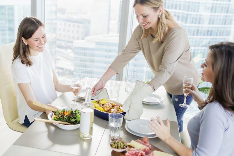 Mujeres jovenes que cenan junto en cocina moderna imagenes de archivo