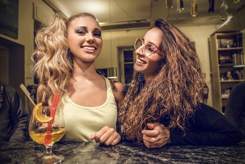 Mujeres jovenes que charlan en un pub imágenes de archivo libres de regalías