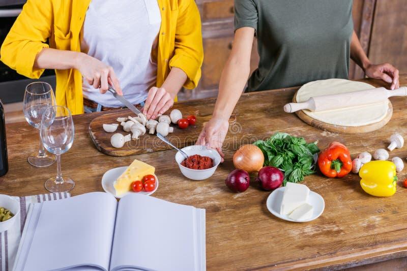 Mujeres jovenes que cocinan la pizza mientras que se une en la tabla de cocina con el libro de cocina en blanco foto de archivo