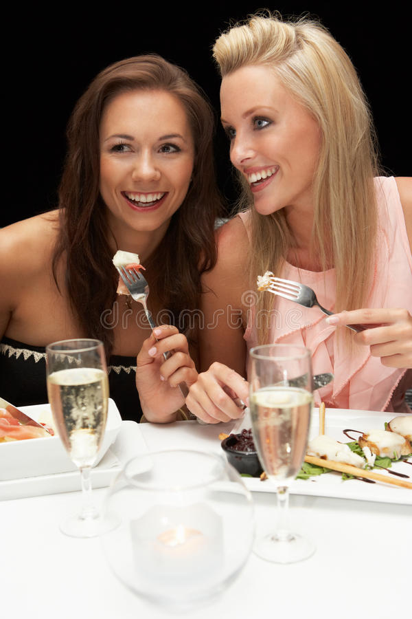 Mujeres jovenes que comen en restaurante foto de archivo