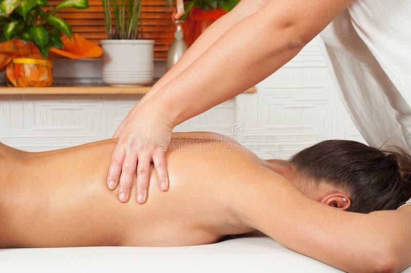 Mujeres jovenes que consiguen masaje posterior en salón del masaje imagen de archivo