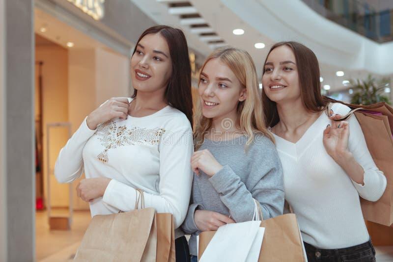 Mujeres jovenes que disfrutan de hacer compras junto en la alameda foto de archivo libre de regalías