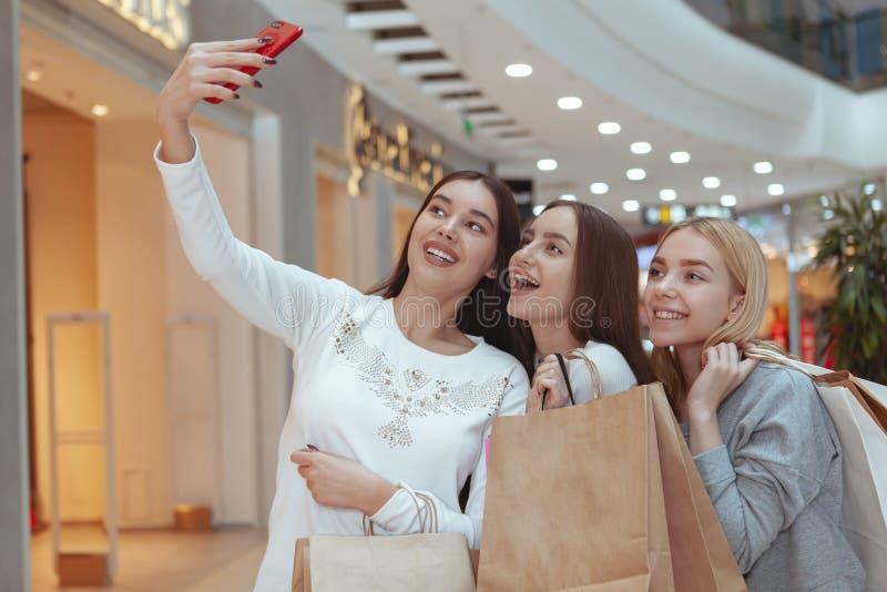 Mujeres jovenes que disfrutan de hacer compras junto en la alameda imagen de archivo libre de regalías