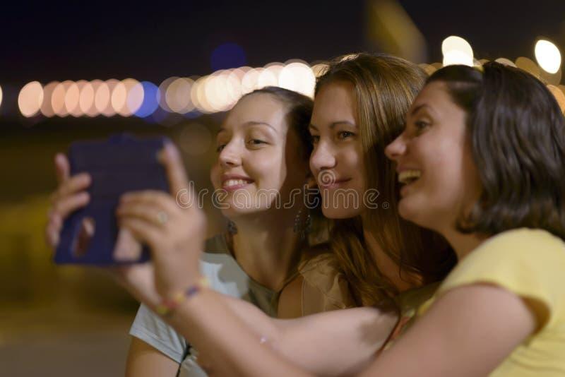Mujeres jovenes que disfrutan del turismo de la noche imagenes de archivo