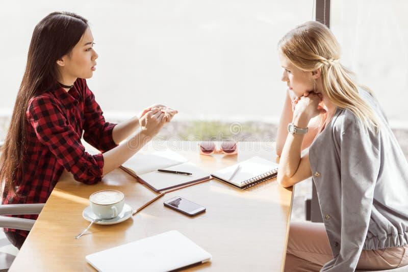 Mujeres jovenes que hablan mientras que teniendo reunión de almuerzo de negocios en café imagenes de archivo
