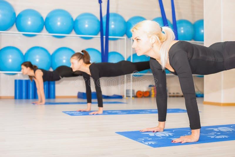 Mujeres jovenes que hacen ejercicio aéreo de la yoga o yoga antigravedad imágenes de archivo libres de regalías