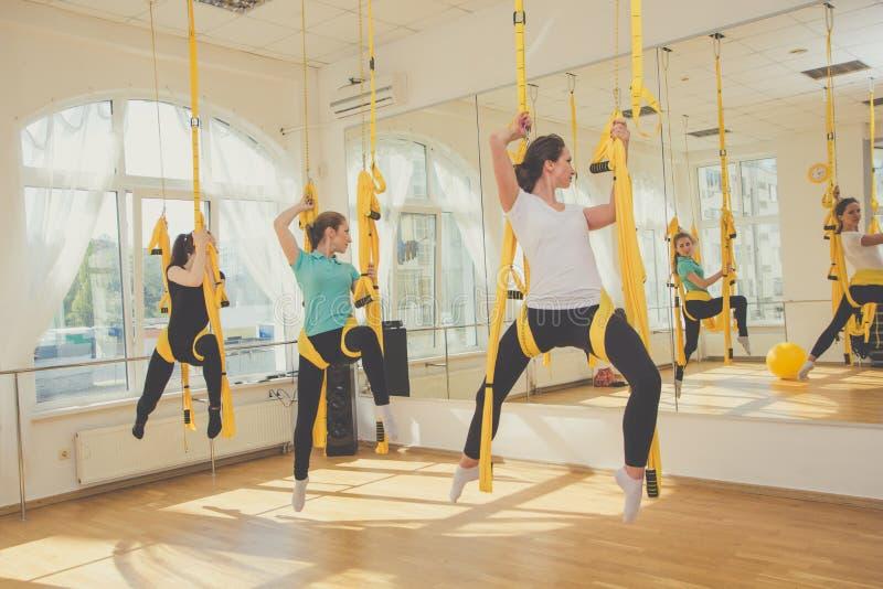 Mujeres jovenes que hacen ejercicios aéreos de la yoga foto de archivo