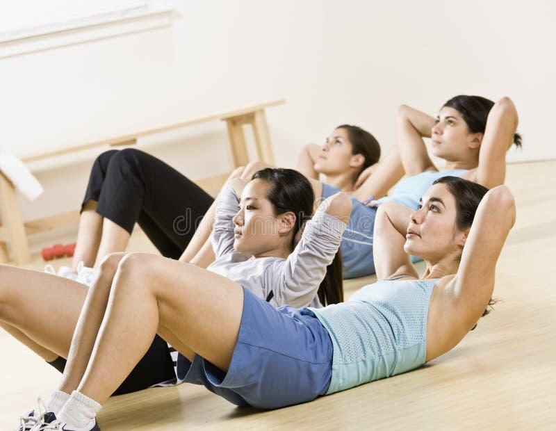 Mujeres jovenes que hacen el sit-ups en clase del ejercicio fotos de archivo