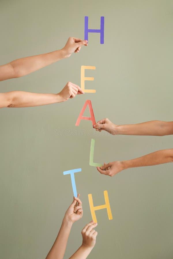 Mujeres jovenes que hacen la palabra SALUD con las letras en fondo del color fotos de archivo libres de regalías