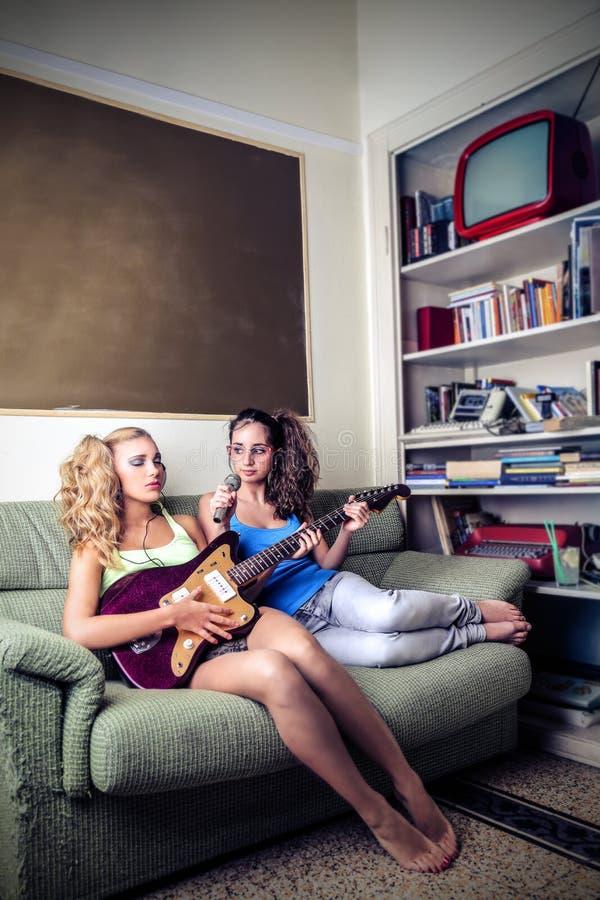 Mujeres jovenes que juegan y que cantan foto de archivo libre de regalías