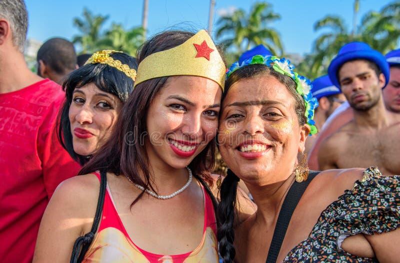 Mujeres jovenes que llevan los trajes de la Mujer Maravilla y a Frida Kahlo que se divierten en Bloco Orquestra Voadora en el par imagenes de archivo