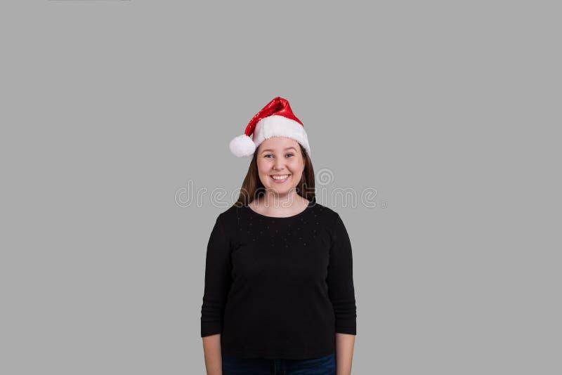 Mujeres jovenes que llevan un sombrero de Santa Claus que sonríe en fondo gris sólido fotografía de archivo libre de regalías