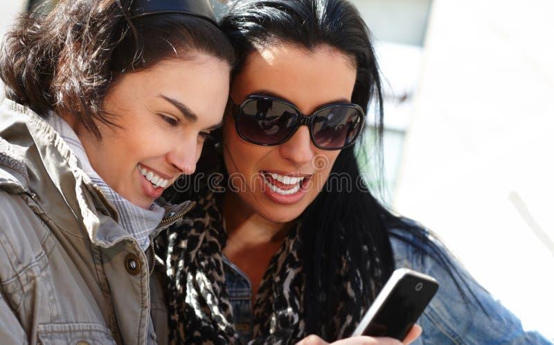Mujeres jovenes que miran smartphone fotografía de archivo